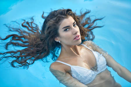 Model in swimming pool outdoors Stock Photo