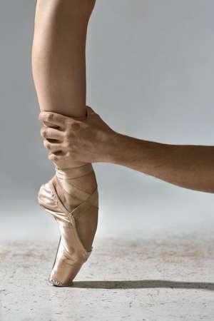 Guy holds ballerinas leg