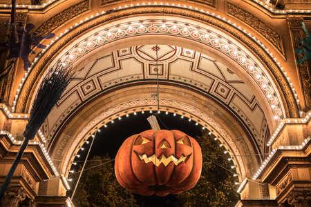 Big Halloween pumpkin hanging in archway Stock Photo