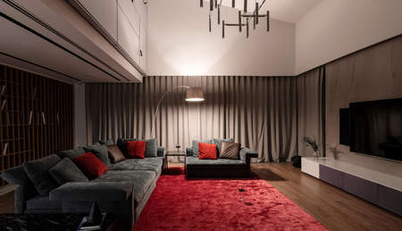 Nice luminous modern room with light walls and a parquet with a red carpet on a floor. There is a sofa and armchair with pillows, small tables, wooden shelves with books, fancy lamps, TV, curtains. Фото со стока