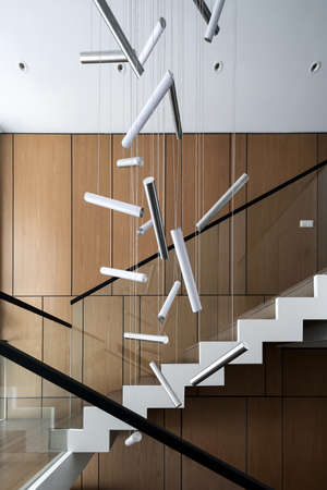 Modern interior with light walls and a stair with wooden rungs and glass railing. There are hanging fancy lamps. Vertical.