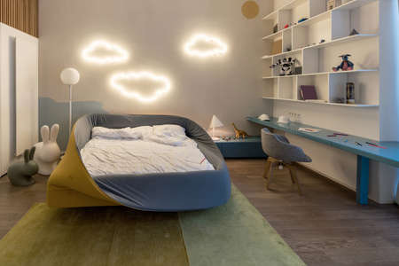 Modern kid's room with luminous fancy cloud lamps on a white wall. There is colorful bed with white linens, blue tabletop with gray chair, white shelves with toys and books, stand with lamp and toys. Фото со стока