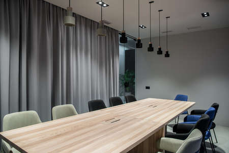 Discussion room with a luminous lamps in an office with gray walls. There are wide wooden tables with multicolor chairs, glass partition with a door and curtain, different lamps, green plants.