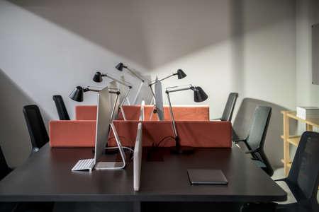 Lieux de travail dans un bureau aux murs gris. Il y a des tables sombres avec des cloisons de couleur pêche et des ordinateurs, des chaises noires, des étagères en bois avec des livres, des lampes lumineuses. Horizontal.