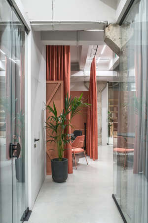 Hall in a luminous office in a loft style with gray walls and concrete columns. There are glass partitions with curtains, meeting zone with orange curtains, tables, chairs, green plant, shelves. Archivio Fotografico