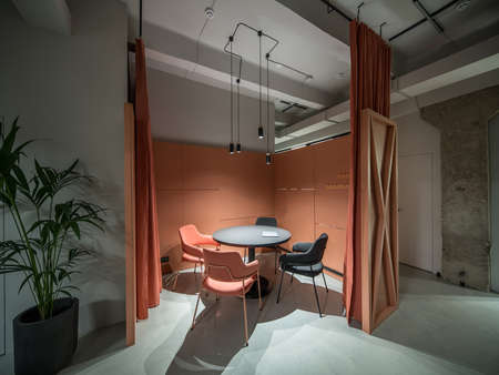 Talk zone with orange curtains in a luminous office with gray walls and concrete column. There is a black round table with a laptop, multicolor chairs, partition, plant in a pot, hanging lamps.