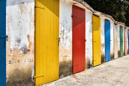 Several old wooden colorful doors on shabby light wall backgroun Banco de Imagens