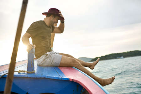 Cheerful man with stubble is sailing on colorful boat