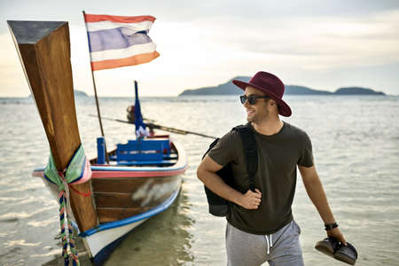 Man with stubble is standing with dark flip flops on shallow water near boat
