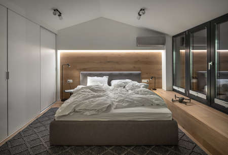 Stylish bedroom in modern style with luminous lamps