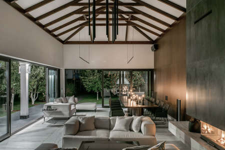Illuminated interior with wooden beams and fireplace Фото со стока
