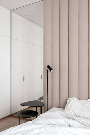 Stylish bedroom in modern style with brown textile wall panel