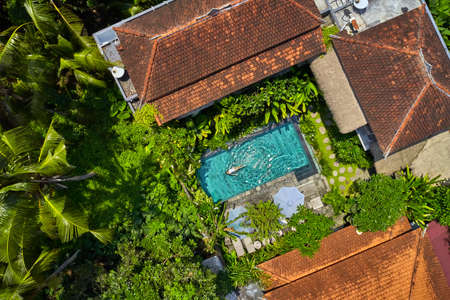 Houses with colorful shingle roofs and pool with swimming woman between palm trees