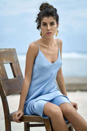 Brunette woman in blue dress posing on chair on sand beach 写真素材