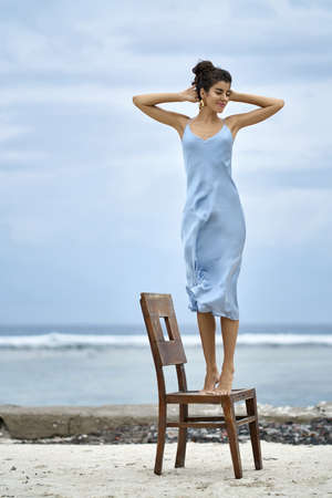 Cheerful barefoot girl with closed eyes in a blue dress and fancy golden earrings stands tip-toes on the wooden chair on the sand beach on the blurred background of the blue sky and the sea. Vertical. Stockfoto