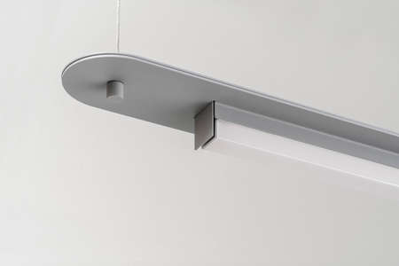 Wonderful metal gray LED lamp is hanging on the light wall background indoors. Closeup horizontal photo.