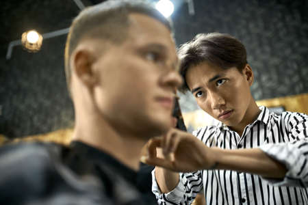 Man is cutting his hair in asian barbershop