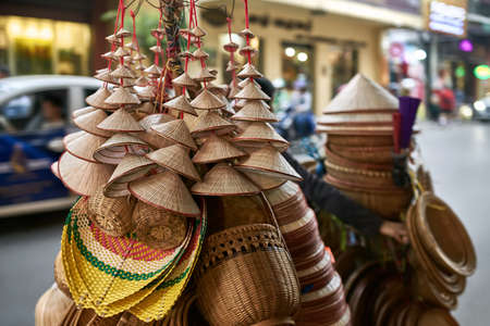 Street seller with asian conical wooden hats and baskets Reklamní fotografie