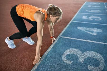 Athletic blonde woman training at indoor stadium Imagens