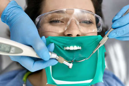 Pretty womans teeth treatment in dental clinic