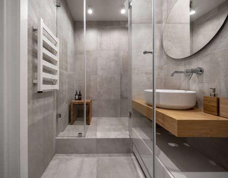 Baño moderno y elegante con paredes y suelo de baldosas claras Foto de archivo
