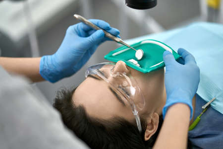 Cute girl in protective glasses and a cheek retractor with a green rubber dam in a dental clinic. Dentist in blue latex gloves examines her teeth with a help of a dental mirror. Closeup.
