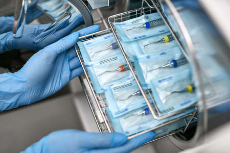 Specialist in blue latex gloves is inserting sealed dental probes inside an autoclave sterilizer. Closeup horizontal photo.