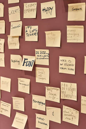 Lot of yellow sticky notes with different writings are hanging on the burgundy wall in the illuminated interior. Closeup. Vertical.