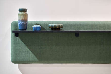 Black wooden shelf with multicolored ceramic decorations on the soft green panel on the light wall background indoors. Closeup horizontal photo. Imagens