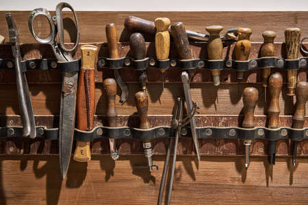 Battered leather craft hand sewing tool set is hanging on the wooden wall in the studio. Closeup horizontal photo.