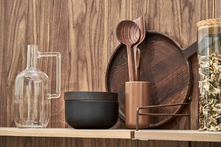 Wooden shelves with wood and ceramic utensil and glass jar and jug on the textured wall background. Closeup horizontal photo.