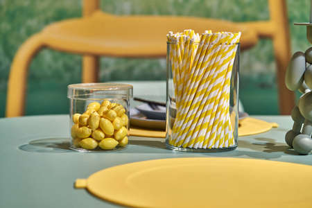 Mint table with multicolored dishes (glasses with small lemon candies and striped yellow white straws, colorful plates with cutlery) and decoration on the blurred background in the studio. Closeup.