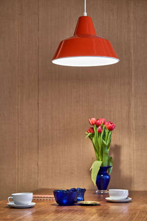 Wooden table with magenta tulips in a blue frosted glass vase, bowls, white cups with saucers, notebook on the textured brown wall background indoors. Above them is hanging a luminous red lamp.