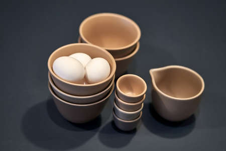 Different sizes ceramic brown bowls and a jug on the dark background in the studio. There are white eggs in the upper bowl. Closeup photo with selective focus. Horizontal.