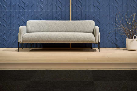 Light soft sofa with black legs on the background of the blue wall with patterns in the illuminated interior with a parquet and a dark carpet on the floor. There is a blossom plant in the white pot.