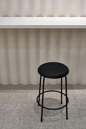 Round black stool on the gray carpet on the waved light wall background in the illuminated interior. Closeup vertical photo.