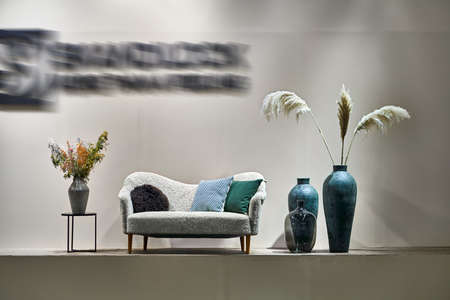 Light soft sofa with multicolored pillows, black stand and different vases with fresh and dried plants on the gray wall background in the illuminated interior. Horizontal.