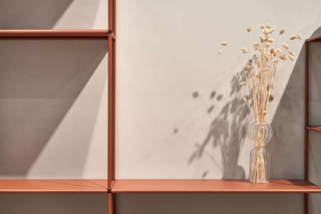 Metal orange shelves with a glass vase with dried plants on the light wall background in the illuminated interior. Closeup horizontal photo.