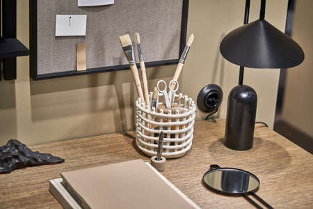 Textured table with books, wicker white holder with paint brushes and scissors, luminous black lamp, small mirror, marker pens, decoration on the background of a soft board on the beige wall indoors. Zdjęcie Seryjne