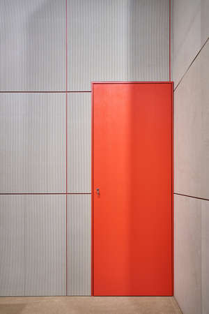 Colorful red door with keys in the keyhole on the background of the striped gray wall in the illuminated interior. Vertical.