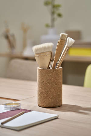 Textured brown holder with few brushes and pencils inside on the wooden table in the illuminated interior. There is a notebook in front of it. Closeup photo with selective focus. Vertical.