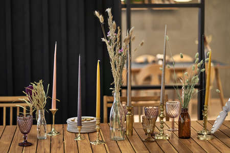 Several empty multicolored frosted glasses, different bottles with dried plants, gold candlesticks with colorful candles, plates with spoons on the wooden table in the illuminated interior. Closeup.