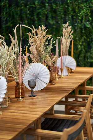 Long wooden table with multicolored frosted glasses, glass vases with dried plants, gold candlesticks with colorful candles and chairs in the illuminated interior. Vertical photo with selective focus. Zdjęcie Seryjne