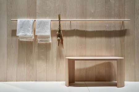 Illuminated interior with textured wooden wall and a light floor. There is a rack with two white towels and dried plants, wood bench. Horizontal. Zdjęcie Seryjne