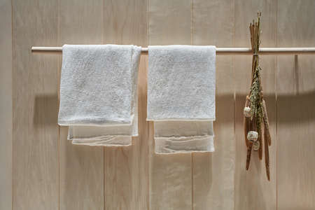 Wood rack with two white towels and dried plants of reed and poppy on the wooden wall background in the illuminated interior. Closeup horizontal photo. Zdjęcie Seryjne
