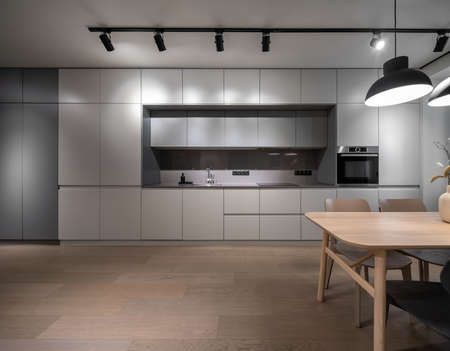 Luminous modern kitchen with light walls and a parquet. There are gray lockers, sink with faucet, dispenser, stove, oven, wooden table with vase with plants and chairs, different lamps. Horizontal.