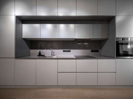 Beautiful illuminated modern gray kitchen with a parquet on the floor. There are lockers and drawers, sink with a chrome faucet, black dispenser, stove, oven, power sockets. Horizontal.