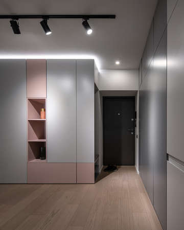 Stylish modern interior with light walls, luminous lamps and a parquet on the floor. There are multicolored lockers with shelves with vases, dark entrance door, black boots. Vertical.