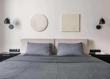 Modern bedroom with white wall with relief pictures. There is a double bed with gray linens and pillows, black nightstands with a book, hanging lamps, power sockets. Horizontal. Zdjęcie Seryjne