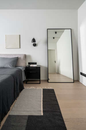 Nice modern bedroom with white walls with a relief picture and a parquet with a multicolored carpet. There is a bed with gray linens and pillows, dark lamps, black nightstand, tall floor mirror. Zdjęcie Seryjne